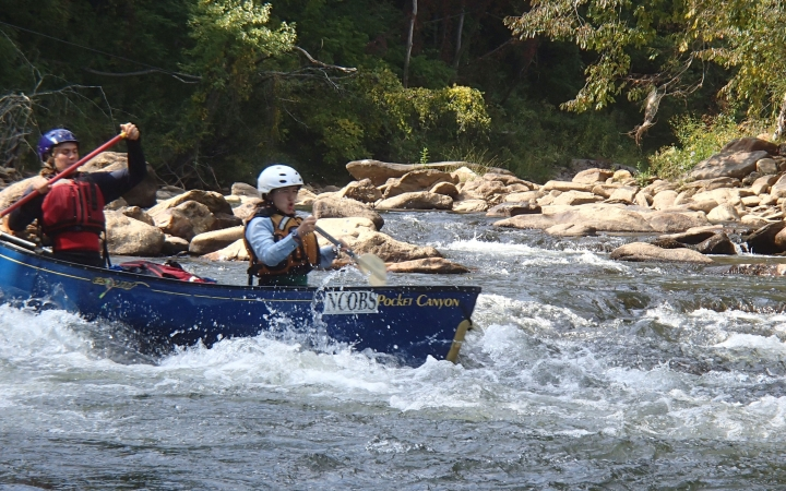 teens navigate whitewater on canoeing trip