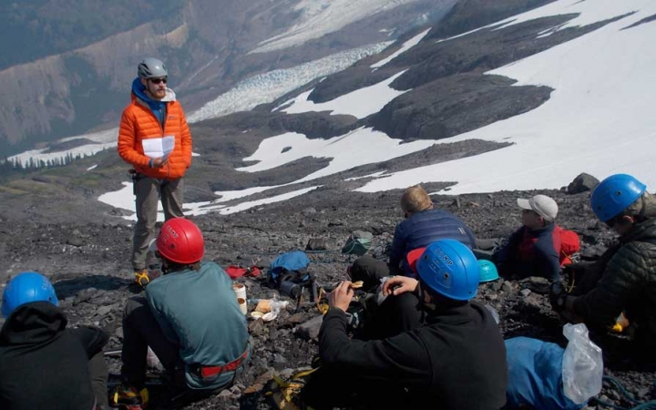 students learning mountaineering skills from instructor
